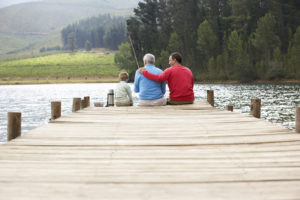 Three generations of family sitting at end of pier