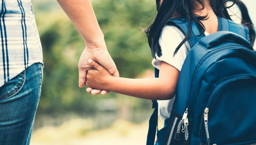 Child with backpack holding adults hand